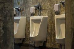 Witte urinoirs in de badkamerstoilet van mensen Stock Afbeeldingen