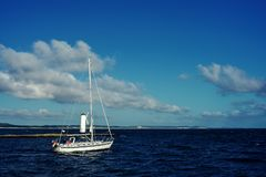Witte varende boot aan de gang gebruikende motor op het achtergrondland stock foto