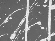 Witte verfplonsen en druppels op een grijze muur stock afbeelding