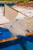 Witte visnetten in de blauwe boot op het strand Stock Afbeelding
