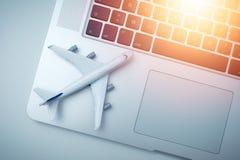 Witte vliegtuigmodel en computerlaptop met zonlicht op witte achtergrond reis, visum en vakantieconcept royalty-vrije stock foto's