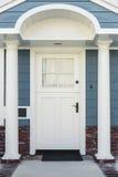 Witte voordeur van klassiek blauw en baksteenhuis stock afbeeldingen