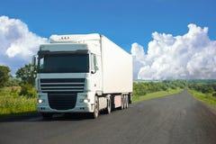Witte vrachtwagen die zich op een weg bewegen Royalty-vrije Stock Afbeeldingen