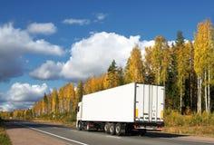 witte vrachtwagen op de herfstweg Stock Foto's