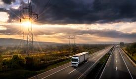 Witte vrachtwagen op een weg bij zonsondergang Stock Foto