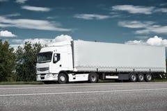 Witte vrachtwagen op weg met blauwe hemel, het concept van het ladingsvervoer Royalty-vrije Stock Foto's