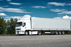Witte vrachtwagen op weg met blauwe hemel, het concept van het ladingsvervoer Stock Foto