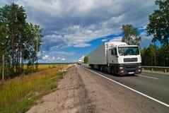 Witte vrachtwagens die op de weg reizen Stock Foto's