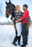 Witte vrouw en Arabische man naast paard in de winter, internationaal paar stock foto