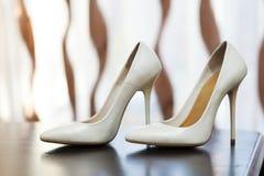 Witte vrouwelijke schoenen met hoge hielen die zich op een lijst bevinden Royalty-vrije Stock Foto's