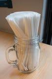 Witte weefsels in violet glas op lijst Stock Foto's