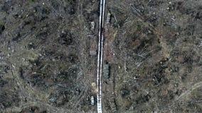 Witte weg in het midden van een vernietigd bos na een orkaan, satellietbeeld stock video