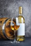 Witte wijnfles met glas voor het proeven en houten vat in donkere kelder royalty-vrije stock afbeelding
