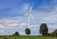 Witte windturbines die elektriciteit in alternatieve vernieuwbaar van de windenergiepost produceren onder blauwe hemel backgroun stock fotografie