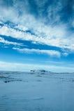 Witte wolk, blauwe hemel, sneeuwgrond, IJsland Stock Afbeeldingen