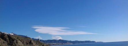 Witte wolk in een blauwe hemel over bergen en overzees Royalty-vrije Stock Afbeeldingen