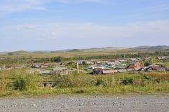 Witte wolken in de heldere blauwe de zomerhemel over dorp met plattelandshuisjes ver weg op de bergen en de gebieden travelling P royalty-vrije stock foto