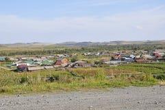 Witte wolken in de heldere blauwe de zomerhemel over dorp met plattelandshuisjes ver weg op de bergen en de gebieden travelling P royalty-vrije stock afbeelding