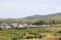 Witte wolken in de heldere blauwe de zomerhemel over dorp met plattelandshuisjes ver weg op de bergen en de gebieden travelling P royalty-vrije stock fotografie