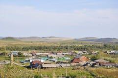 Witte wolken in de heldere blauwe de zomerhemel over dorp met plattelandshuisjes ver weg op de bergen en de gebieden travelling P stock fotografie