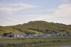 Witte wolken in de heldere blauwe de zomerhemel over dorp met plattelandshuisjes ver weg op de bergen en de gebieden travelling P stock foto