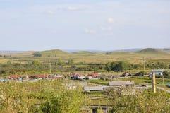 Witte wolken in de heldere blauwe de zomerhemel over dorp met plattelandshuisjes ver weg op de bergen en de gebieden travelling P stock afbeelding