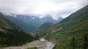 Witte wolken met een rivier in de bergen Een groene kloof, een mooi landschap van bergen royalty-vrije stock foto