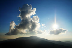 Witte wolken op blauwe hemel boven heuvels Stock Afbeeldingen