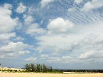 Witte wolken op de blauwe hemel over het strand van het land Stock Foto's