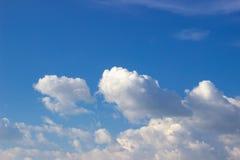 Witte wolken op een zonnige dag, tegen de blauwe hemel stock foto