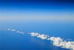 Witte wolken tussen blauwe hemel en blauwe overzees royalty-vrije stock afbeelding