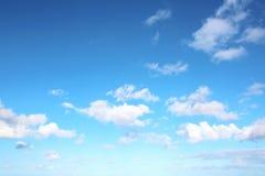 Witte wolken van diverse vormen tegen de blauwe hemel en de zon boven de oppervlakte van de oceaan stock fotografie