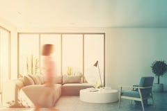 Witte woonkamer met een blauwe bank, voorzijde, meisje Stock Afbeelding