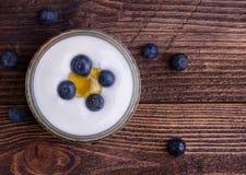 Witte yoghurt in glaskom met bosbessen op houten rustieke lijst close-updetail stock afbeeldingen