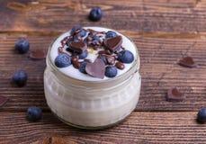 Witte yoghurt in glaskom met gehele bosbessen op houten rustieke lijst close-updetail royalty-vrije stock afbeeldingen