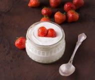 Witte yoghurt in glaskom met lepel en starwberries op plattelander Stock Foto's