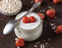 Witte yoghurt in glaskom met lepel en starwberries op plattelander Stock Afbeeldingen