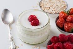 Witte yoghurt in glaskom met lepel en starwberries op wit Stock Foto