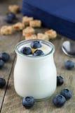 Witte yoghurt in glaskruik met honing stock foto