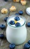 Witte yoghurt met bosbessen in glaskom stock afbeeldingen