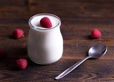 Witte yoghurt met frambozen in glaskom stock afbeeldingen