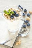 Witte yoghurt met musli en bosbessen royalty-vrije stock afbeeldingen