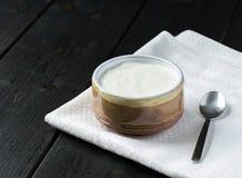 Witte yoghurt in naar huis bewerkte kom op houten zwarte achtergrond royalty-vrije stock afbeelding