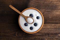 Witte yoghurt in natuurlijke houten kom met bosbessen Hoogste mening over rustieke achtergrond royalty-vrije stock foto's