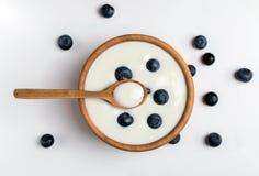 Witte yoghurt in natuurlijke houten kom met bosbessen Hoogste Mening over Witte Achtergrond stock afbeeldingen