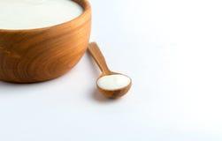 Witte yoghurt in natuurlijke houten kom met houten lepel op witte achtergrond royalty-vrije stock fotografie