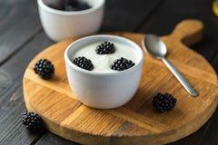 Witte yoghurt in witte kom op houten bureau royalty-vrije stock fotografie