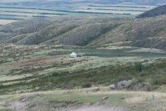 Witte yurt op de heuvel Reusachtige ruimte Bergen die in de wolken worden omhuld stock afbeeldingen