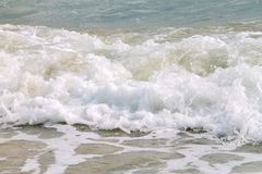 Witte zachte golf rollende plons op leeg tropisch zandig strand in zonnige dag stock foto