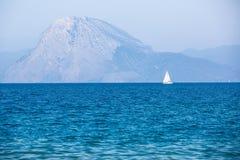 Witte zeilboot in het blauwe overzees met bergen stock afbeeldingen
